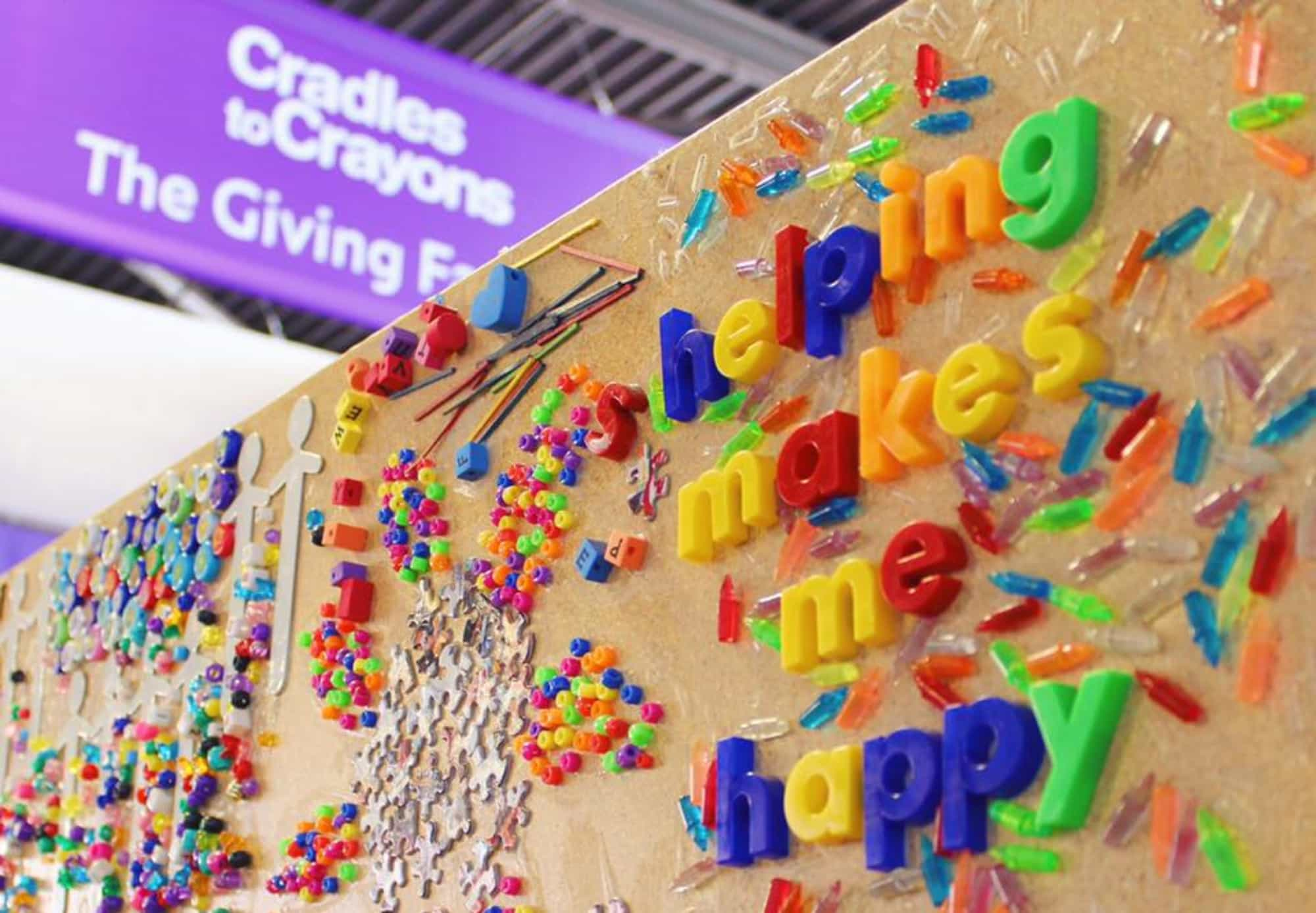 "A board at the giving factory that reads in magnet letters, ""helping makes me happy""."